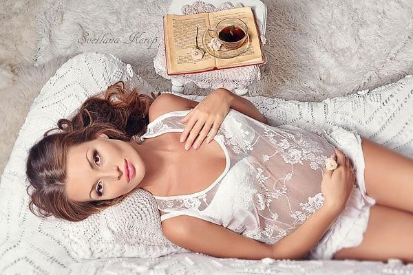 Беременная женщина готовится к эпиляции лежа на кровати