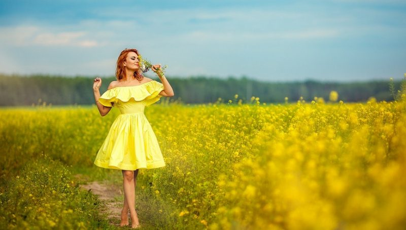 Девушка летом идет по полю в желтых цветах