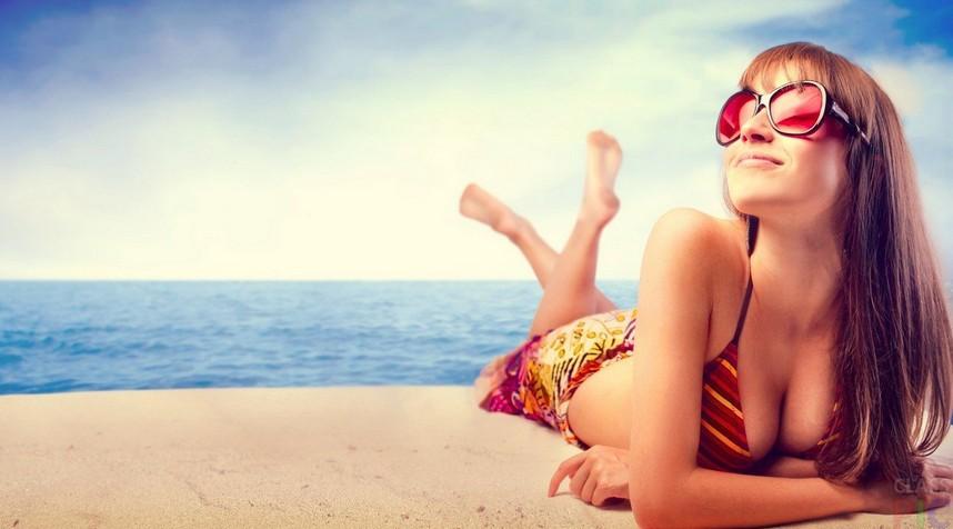 Девушка загорает на море
