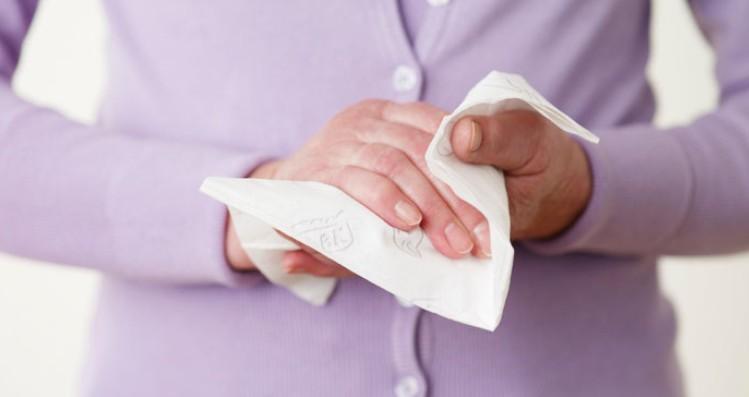 Девушка вытерает руки салфеткой