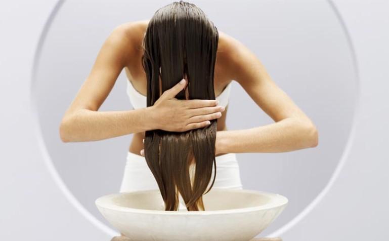 Девушка ополаскивает волосы
