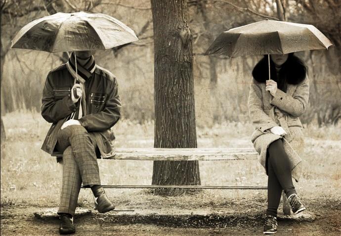 Девушка и мужчина сядят на лавочке